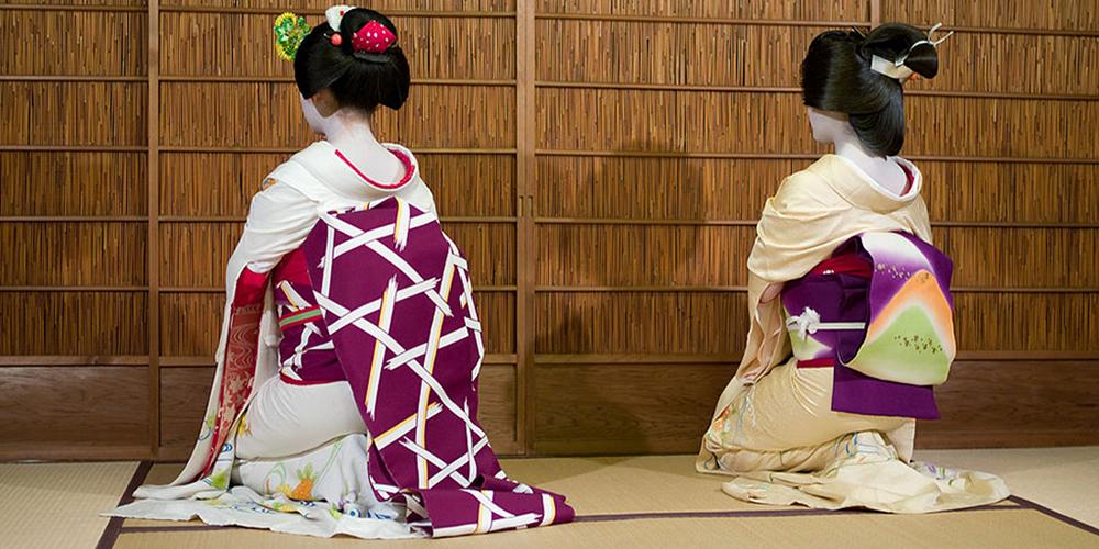 À gauche une maiko, à droite une geisha, toutes deux agenouillées et de dos.